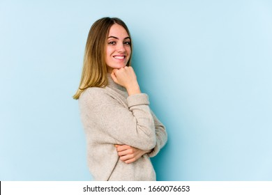 Young caucasian woman isolated on blue background smiling happy and confident, touching chin with hand.