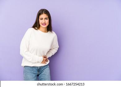 紫の背景に腹痛、胃痛を持つ白人の若い女性。