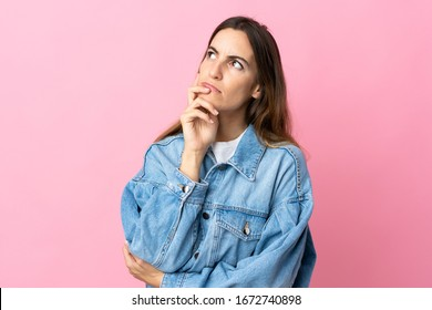 Young caucasian woman isolated on pink background having doubts while looking up