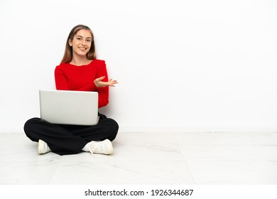 Young caucasian woman with a laptop sitting on the floor presenting an idea while looking smiling towards