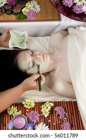 A young Caucasian woman lies on a massage table with a candle and flowers with a face mask being applied.