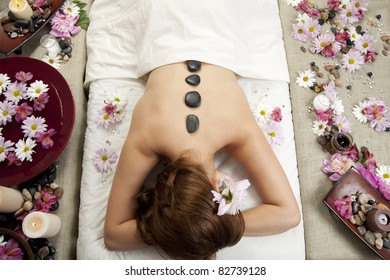 A young Caucasian woman lies on a massage table with hot stones on her back and candles and flowers surrounding her.