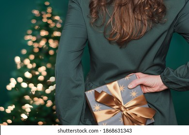 Young caucasian woman with long hair hiding gift box with golden ribbon behind her back. Christmas tree with lights on background.
