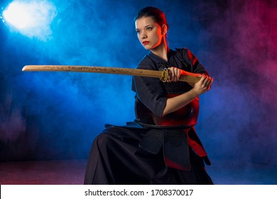 young caucasian woman love kendo fighting, hold bamboo sword in hands, practice fighting isolated over smoky space
