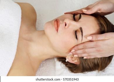 Young caucasian woman lying down receiving head massage