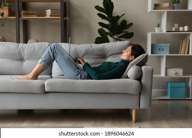 Young Caucasian woman lying on couch in living room work online on laptop gadget. Millennial female relax rest on sofa at home look at computer screen text message on device. Communication concept.