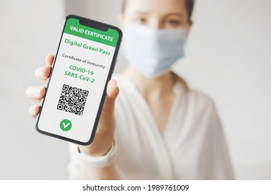Young caucasian woman in mask holding smartphone with digital green pass and QR code on the screen. Health passport or certificate of immunity. Traveling without restrictions. Vaccinated person