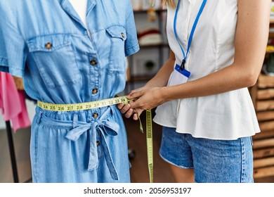 Young caucasian woman measuring manikin at clothing store
