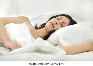 Young Caucasian woman with medium-long black hair resting/sleeping in bed