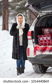 Young Caucasian woman in mink fur stands full-length near own car and drinks hot tea. Walking in winter forest