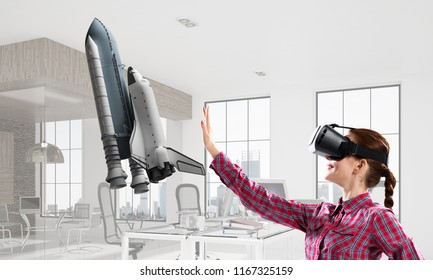 Young caucasian woman in modern office interior trying virtual reality helmet and viewing space shuttle. Mixed media