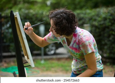 young caucasian woman painting on canvas outside