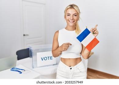 Jeune femme caucasienne à l'élection politique tenant le drapeau de la france souriant, pointant du doigt et main sur le côté