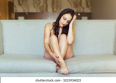 Young caucasian woman poses nude on sofa under natural window light