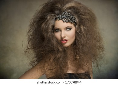 young caucasian woman posing in fashion portrait with voluminous curly hair-style, glitter accessory in the hair and cute make-up