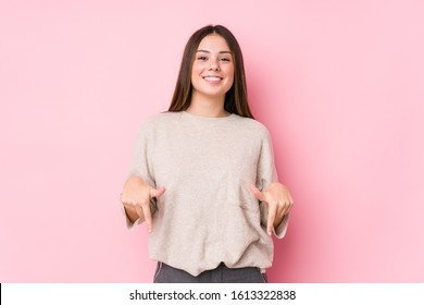 Young caucasian woman posing isolated points down with fingers, positive feeling.