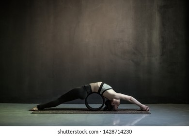 Young caucasian woman practices yoga asana Matsyasana fish pose variation using wheel props. Studio shot