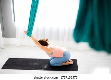 Young Caucasian woman practicing aerial yoga in class with a light, white background. Part of a studio yoga workout sequence and training routine.