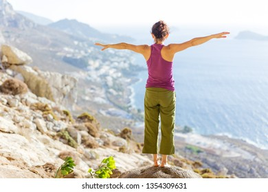 Young Caucasian woman practicing yoga or working out while standing on cliff on sea coast