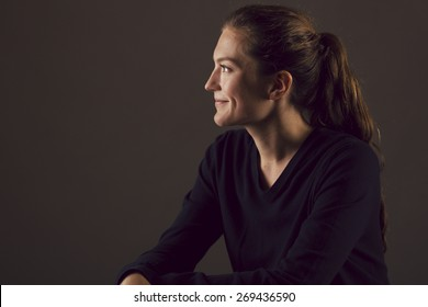 Young Caucasian woman in profile looking off camera and smiling with Rembrandt lighting