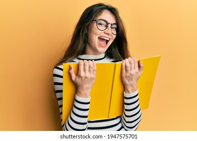 Young caucasian woman reading a book wearing glasses smiling and laughing hard out loud because funny crazy joke.