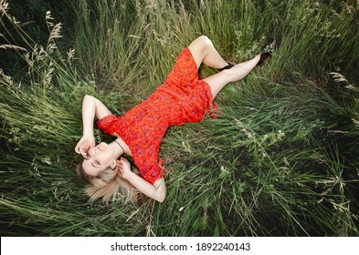Young caucasian woman in red dress daydreaming laying on the green grass outdoors wideangle full length shot