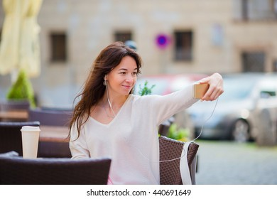 Young caucasian woman sending message and taking self portrait in outdoor cafe. Happy girl enjoy summer time in Europe vacation