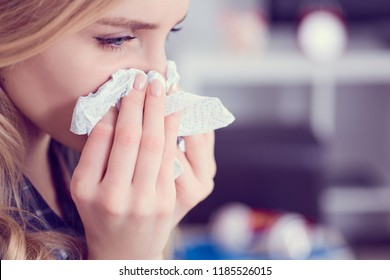 Young Caucasian woman siitng on sofa with running nose and tissues. Concept of illness and resting.