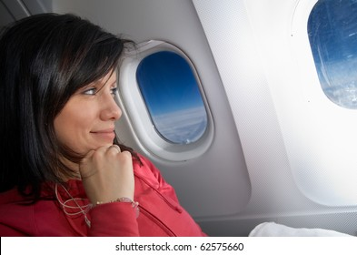 young caucasian woman is sitting in the airplane and dreaming