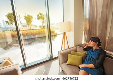 a young caucasian woman sitting in her living room on a sofa looking out through window