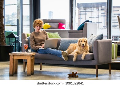 Young caucasian woman sitting on a couch, working on a laptop