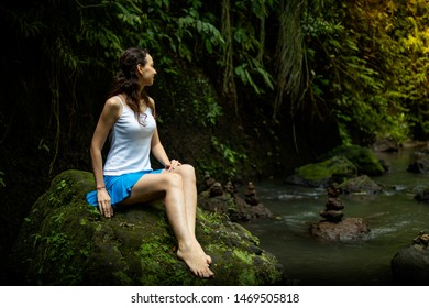 Young Caucasian woman sitting on the rock, enjoying river view near waterfall. Vacation in Asia. Calm and relaxing atmosphere. Tropical nature landscape. Near Tibumana waterfall Ubud, Bali, Indonesia.