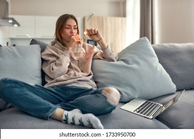 Young caucasian woman sitting on the couch at home and lighting cannabis in the bowl of glass water pipe or bong. Cannabis and weed legalization concept. Horizontal shot