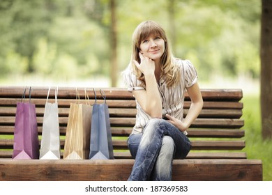 Young caucasian woman sitting on park bench with shopping bags