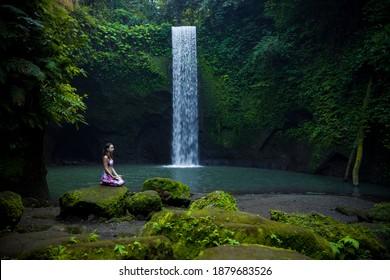 Young Caucasian woman sitting on the stone near the waterfall in Vajrasana or Diamond pose. Hands in gyan mudra. Tropical landscape. Yoga and pranayama concept. Relaxing mood. Tibumana waterfall, Bali