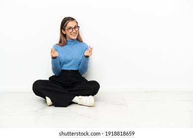 Young Caucasian woman sitting on the floor making money gesture
