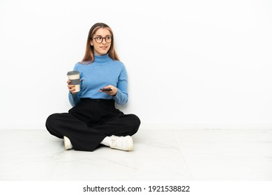 Young Caucasian woman sitting on the floor holding coffee to take away and a mobile while thinking something