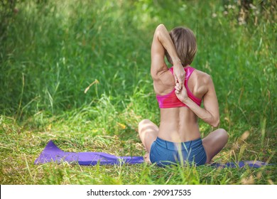 Young Caucasian woman sitting and stretching her arms behind her back