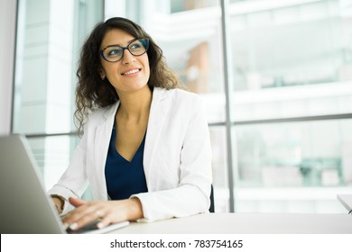 young Caucasian woman smiling business woman working behind laptop at office