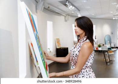Young caucasian woman standing in an art gallery in front of painting displayed on white wall