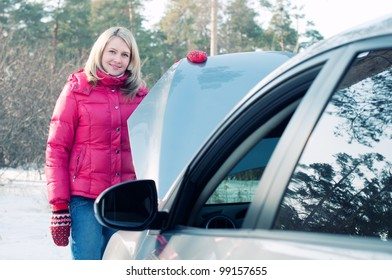 Young caucasian woman standing by the car with bonnet opened