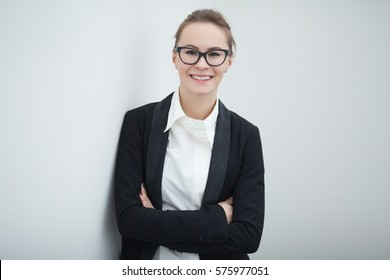 Young caucasian woman standing in the office with crossed arms.