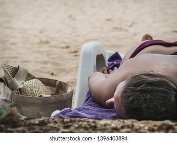Young caucasian woman sunbathing on the Mirissa beach. Sri Lanka, March 17, 2019.