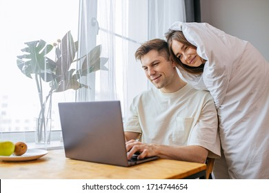 young caucasian woman support husband during his freelance work at home, female wrapped only in blanket leaned on man, husband sit with laptop and smile. in the morning