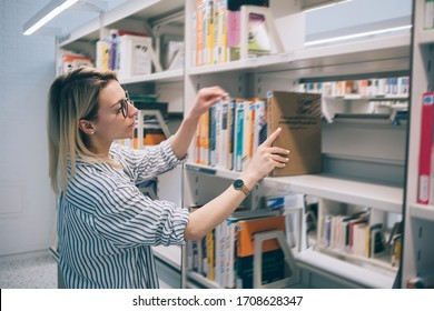 Young Caucasian woman taking book from shelf in library searching literature for self education in college, intelligent female librarian 20 years old putting best seller to bookcase during work