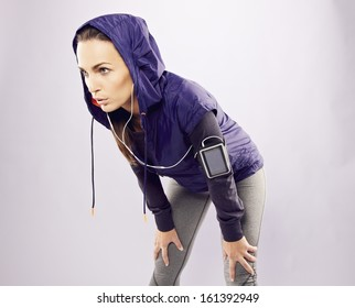Young caucasian woman taking breath after jogging. Female athlete resting with hands on knees and looking away over grey background