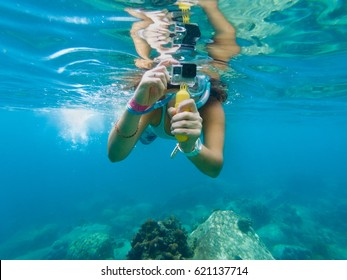 A young caucasian woman taking pictures under water.  Koh Tao, Thailand.
