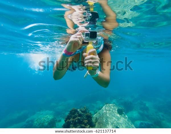 Eine junge Kaukasierin, die unter Wasser fotografiert.  Koh Tao, Thailand.