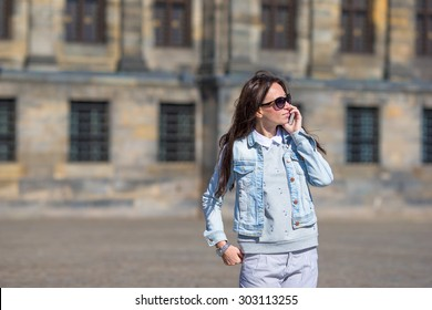 Young caucasian woman talking by cell phone at old streets in european city