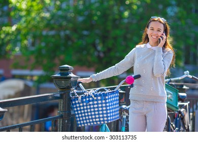 Young caucasian woman talking by cell phone on bridge in european city